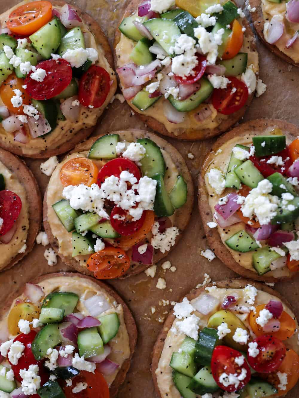 GREEK SALAD FLATBREADS - INGREDIENTS6 gluten free flatbread rounds4 cucumbers, diced1 cup tomatoes, halved1/2 cup red onion, chopped3 tablespoons olive oil3 tablespoons champagne vinegar (or red wine vinegar)Salt and pepper to tasteFeta cheese to crumble on topHummus, to spread on the rounds