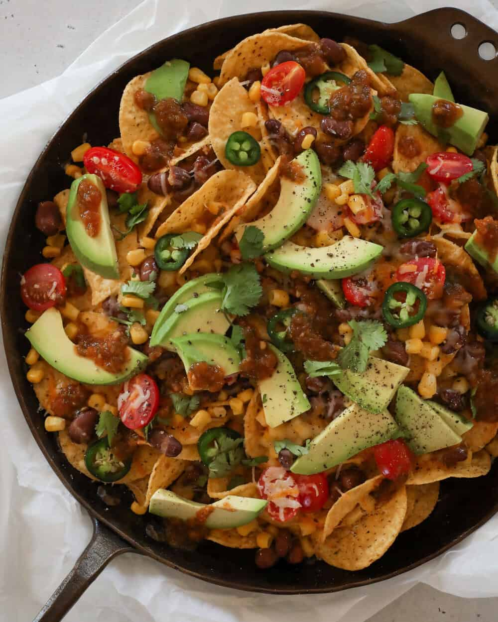 SKILLET NACHOS - INGREDIENTS1 9-12oz bag tortilla chips of choice (I usually make this with @sietefoods chips)1/2 can pinto beans, drained and rinsed1/2 can corn, drained and rinsed3/4-1 cup vegan shredded Mexican cheese1 avocado, sliced1/2 cup salsa1/2 cup vegan queso (I used @eatzubi)Sliced jalapeño pepper, chopped cilantro, and cracked pepper (optional