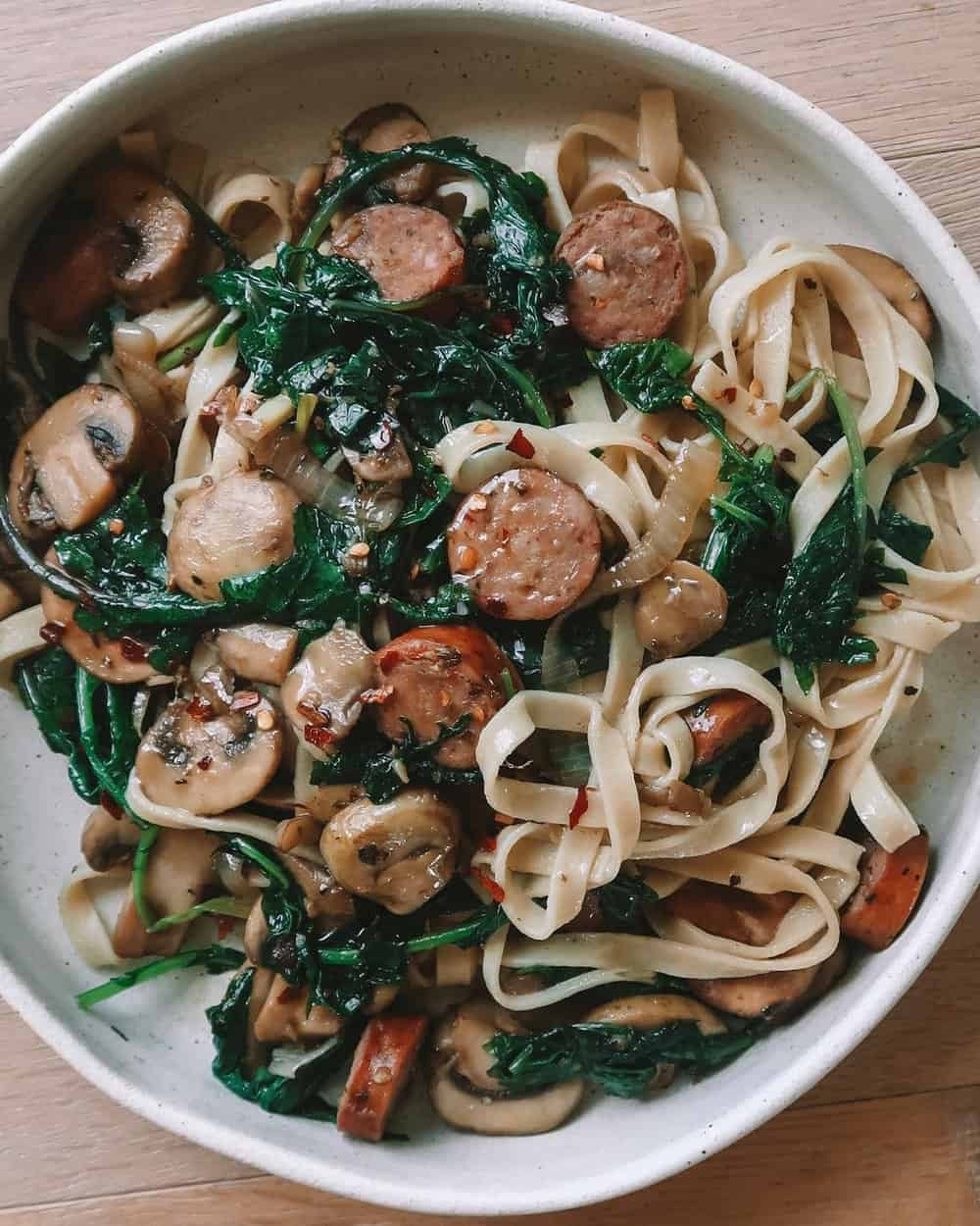 ONE POT SPICY SAUSAGE & BABY KALE FETTUCCINE - INGREDIENTSone large shallotthree cloves garlic1 package of sausage of choice1 tb Italian seasoning3 tb avocado oil2 cups baby kalejuice or one lemon1 package sliced white mushroomscrushed red pepper to tastepasta of choice (I used @capellos fettuccine)