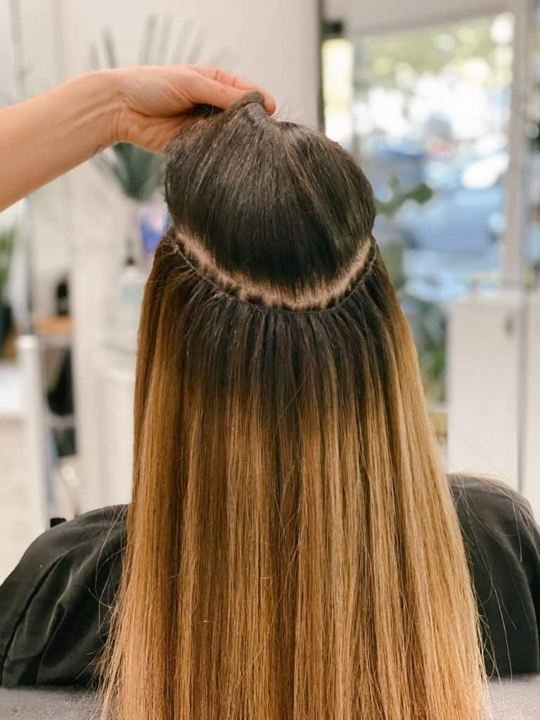 photo of a woman with natural beaded row hair extensions being installed